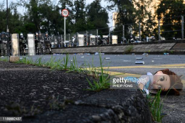 Doll is seen on the ground as police fire tear gas at protesters in Tai Po district during a general strike in Hong Kong on August 5 as simultaneous...