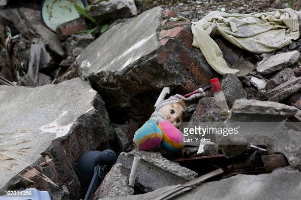 A doll lies between rubbles of a collapsed building at the earthquake memorial park at the new Beichuan town in Sichuan province on April 24 2013 in...