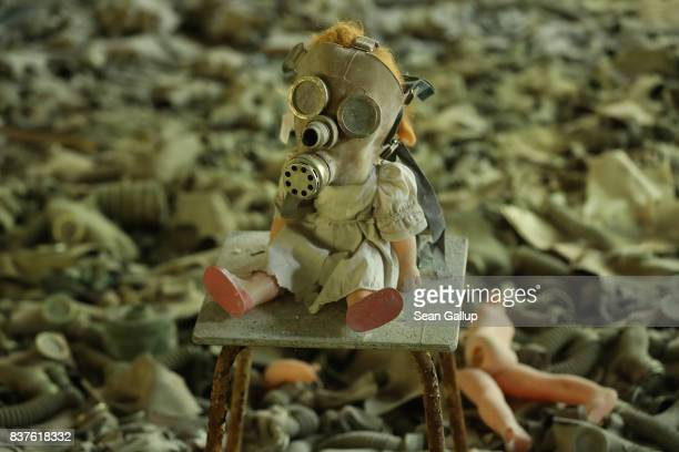 Doll, likely arranged by a tourist, dressed with a gas mask sits on a chair among hundreds of gas masks lying on the floor of abandoned School Number...