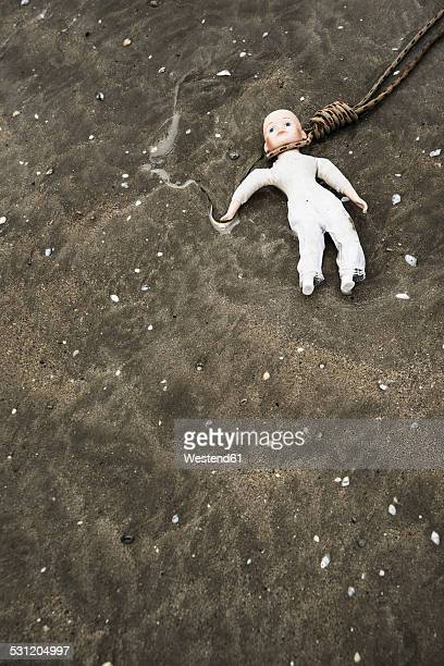doll lying on wet sandy beach with rope on the neck - cervix fotografías e imágenes de stock