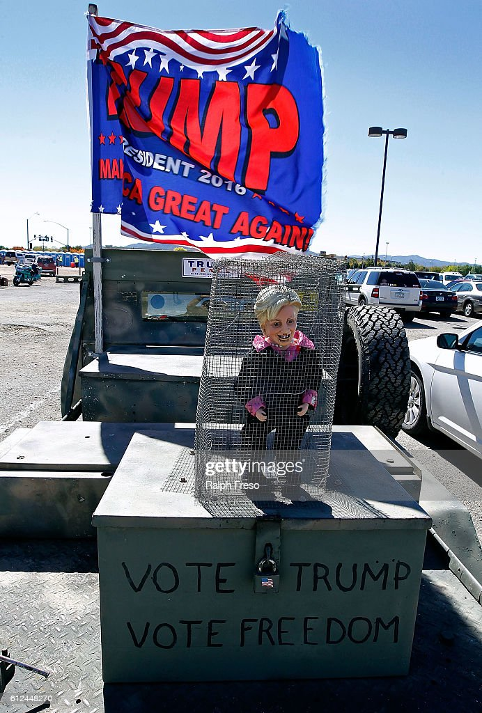 A doll of Hillary Clinton stands in a cage as a Trump flag flies overhead prior to Republican presidential nominee Donald Trump speaking at a campaign rally on October 4, 2016 in Prescott Valley, Arizona. Trump has announced that he will be live tweeting during the vice presidential debate.