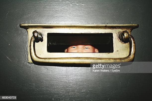 doll seen through closed door hole - dolly golden stock pictures, royalty-free photos & images