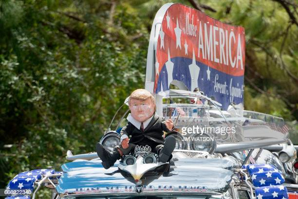 A doll that looks like US President Donald Trump sits upon a supporters car outside Trump International Golf Club as the President's motorcade passes...
