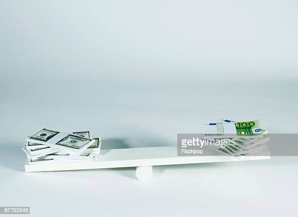 Dollar and Euro notes balancing on seesaw
