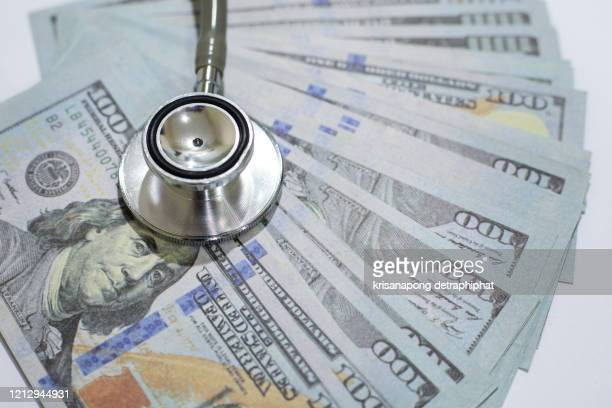 dollar and stethoscope - patient protection and affordable care act stock pictures, royalty-free photos & images