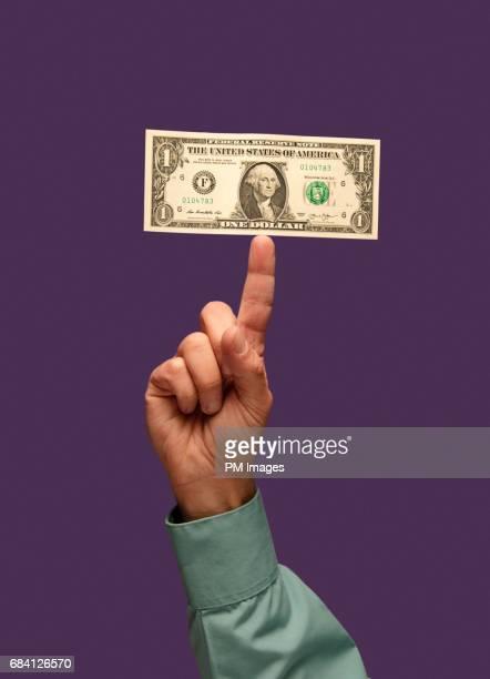 Dollar balanced on finger