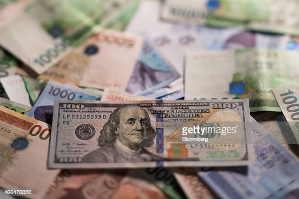 A US 100 dollar banknote sits on a pile of South Korean won banknotes in this arranged photograph in Seoul South Korea on Monday March 16 2015 South...