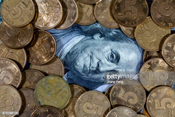 US dollar banknotes covered by Chinese 50cent coins arranged for photography Trump administration officially declines to label China currency...