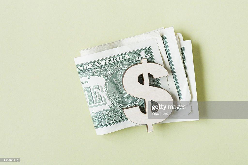 Dollar banknotes in dollar symbol shaped money clip, studio shot : Stock Photo
