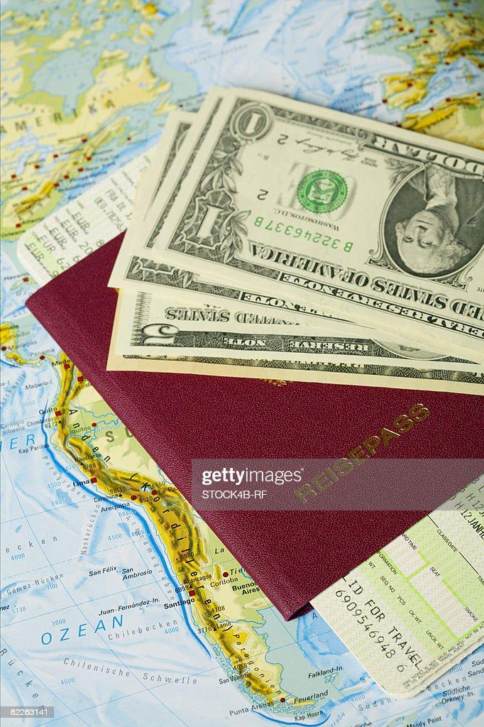 Dollar banknotes, passport an flight ticket on a map : Stock Photo
