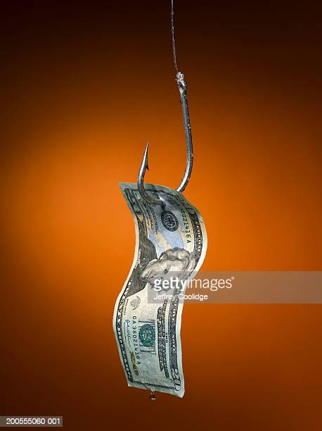 Dollar bill hanging from fish hook, close-up