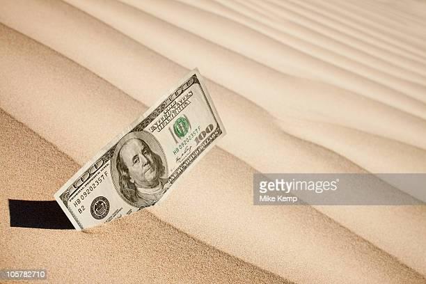 100 dollar bill in sand