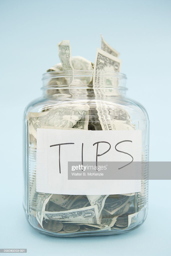 US dollar bills and coins in tip jar : Stock Photo