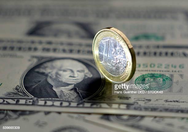 Dollar bills and Euro coin