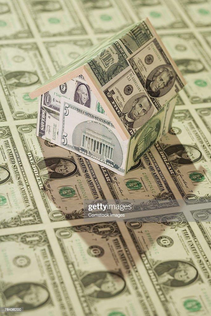 Dollar bills and model house made of money : Stockfoto