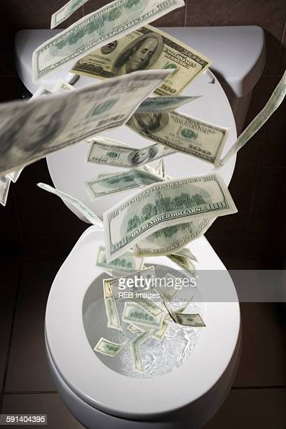 Dollar bills falling into toilet
