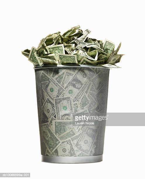 Dollar bills in wire waste basket, on white background