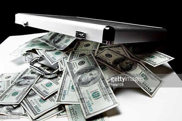 $100 dollar bills spilling out of suitcase. - stealing crime stock pictures, royalty-free photos & images