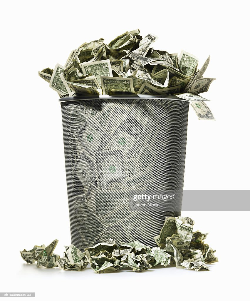 Dollar bills spilling out of wire waste basket : Stock Photo