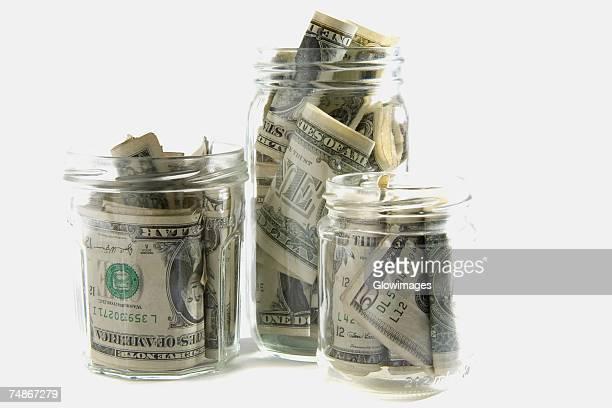 Dollar bills squashed into three jars
