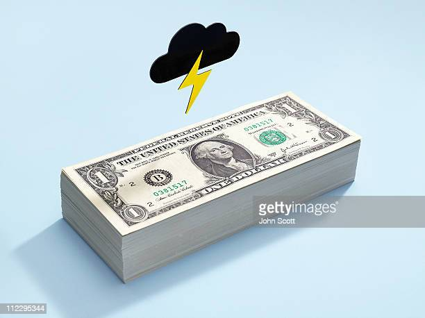 Dollar bills with a dark cloud above