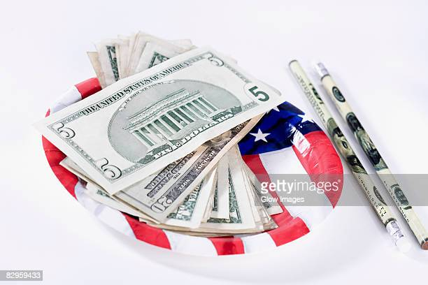 US dollar bills with an American flag and pencils