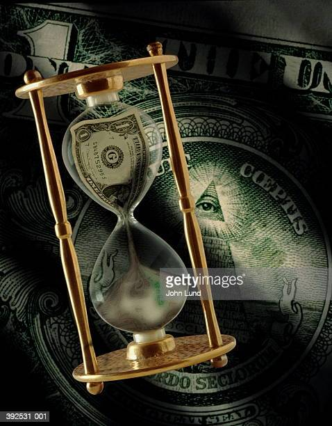 'Dollar' hourglass with dollar bill in background (Digital Composite)