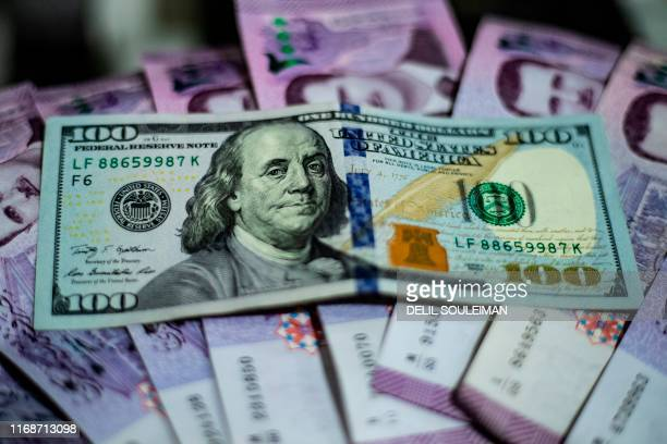 A US dollar note is placed on a stack of Syrian pounds at a market in the Kurdishmajority city of Qamishli in northeast Syria on September 10 2019...