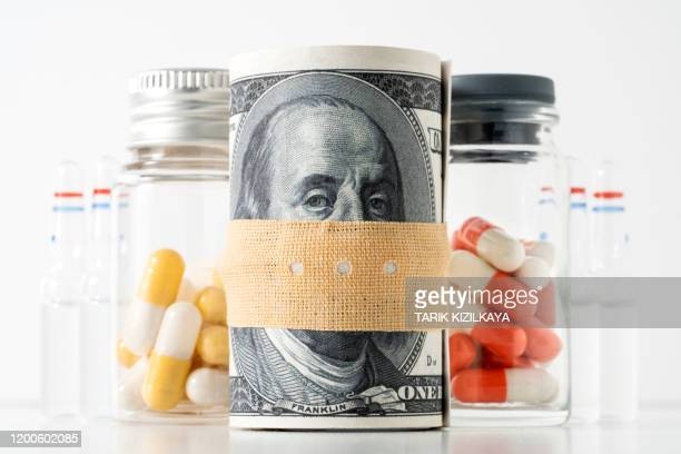 dollar roll and medicine - expense stock pictures, royalty-free photos & images