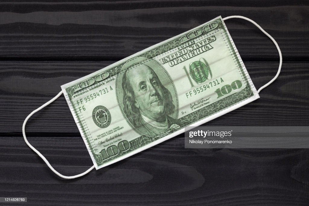 dollar shaped medical mask on a dark background the concept of making money on infection protection : Stock Photo