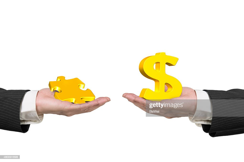 Dollar sign and puzzle piece with two hands : Stock Photo