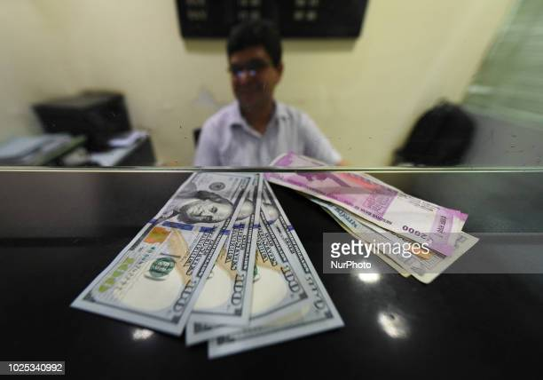 Dollars and Indian Rupee kept for exchange at a forex bureau after the rupee hit a new alltime low of 7047 against US Dollars in New Delhi on Aug 30...