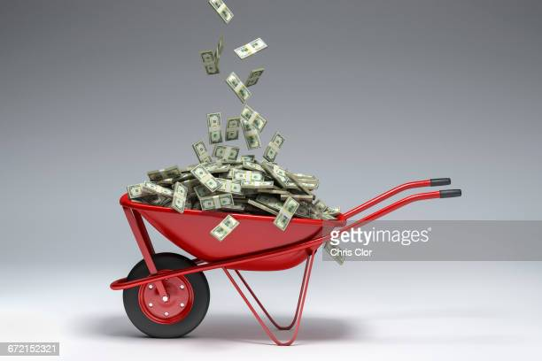 dollars falling into red wheelbarrow - wheelbarrow stock photos and pictures