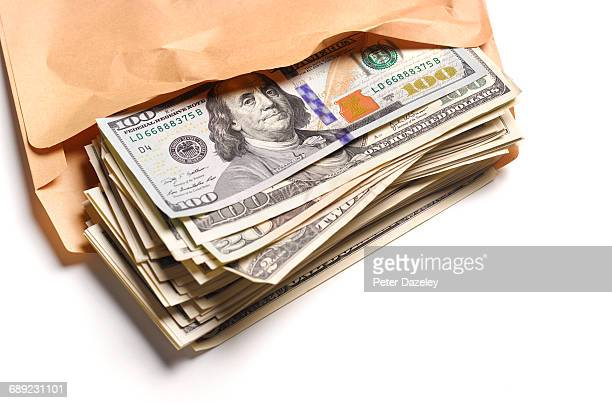 us dollars in brown envelope - corruption stock pictures, royalty-free photos & images