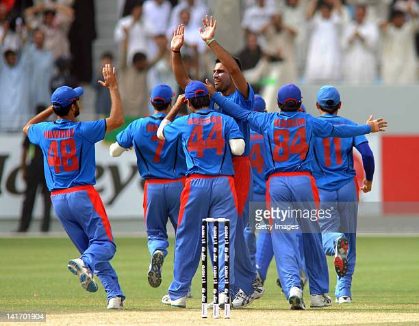 Dollat Zadran of Afghanistan is mobbed by teammates after taking the wicket of Craig Williams of Namibia during the ICC World Twenty20 1st Qualifying...