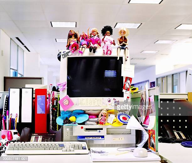 Dolls and stickers on computer monitor in office