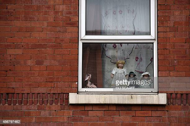 Dolls are displayed in an upper floor window of a house in the Eastwood area of Rotherham South Yorkshire North England on October 6 2014 An inquiry...