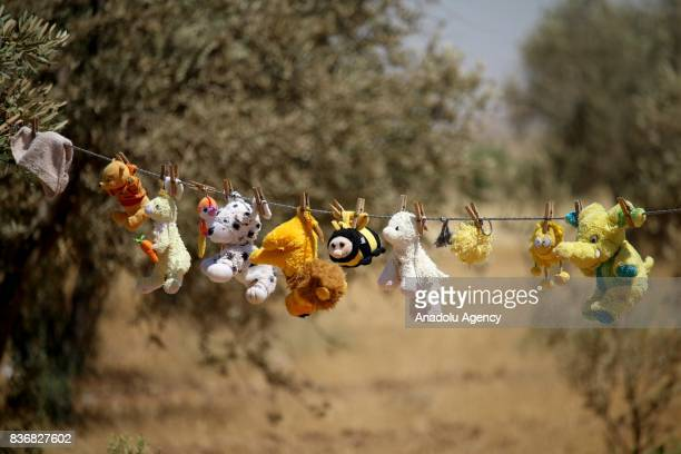 Dolls are seen on a laundry rope near tents during civil war in Daraa Syria on August 17 2017