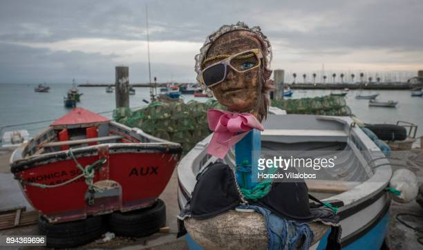 A doll's head decorates a fishing dinghy at commercial fishermen's area facing Praia da Baia on December 14 2017 in Cascais Portugal From the Middle...