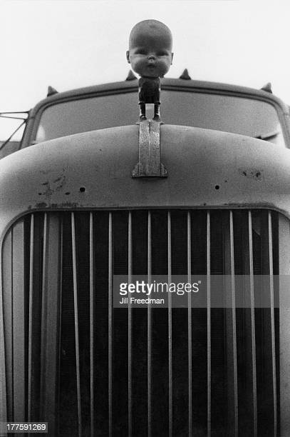 A dolls head is used to replace the hood ornament on a truck in New York City 1970