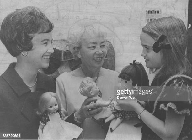 Dolls of three generations are shown by Mrs William Kuhn left 431 Elm St her mother Mrs Henry Hough center 348 Franklin St and Mrs Kuhn's daughter...