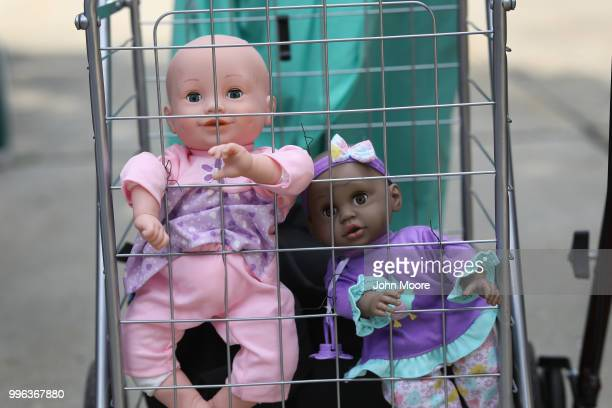 Dolls stand in a shopping cart as protesters rally against the separation of immigrant families in front of a US federal court on July 11 2018 in...