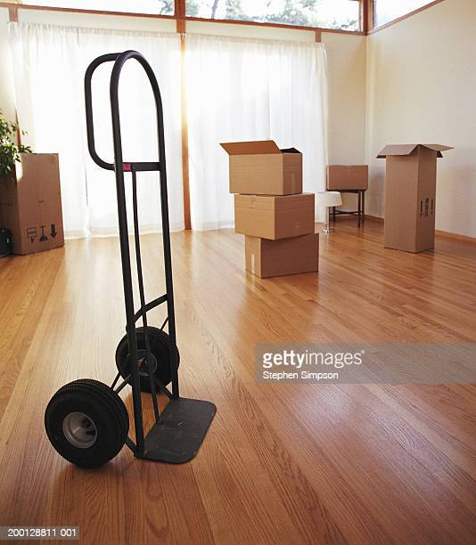 dolly and moving boxes in empty room of house - sack barrow stock pictures, royalty-free photos & images