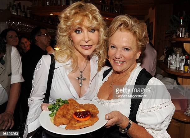 Dolly Buster and Rosi Schipflinger show a Schnitzel durng the 'Schnitzelessen Party' at Rosis Sonnenbergstuben on January 23 2010 in Kitzbuehel...
