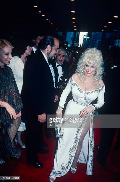 Dolly Parton wearing a beaded white dress going to a formal event circa 1970 New York