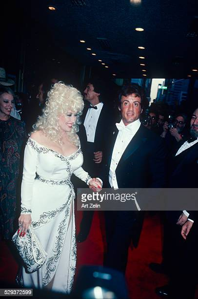 Dolly Parton wearing a white beaded dress with Sylvester Stallone in a tux circa 1970 New York