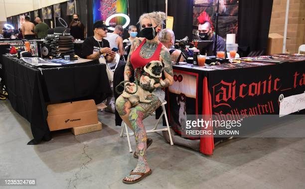 Dollydestruction sits with her dog Milo at husband Hollis Cantrell's Iconic Tattoo booth at the Golden State Tattoo Expo, presented by Inked...