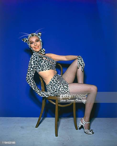 Dolores del Rio Mexican actress poses wearing a leopard skin costume with matching shoes and fishnet stockings while sitting in a chair in a studio...