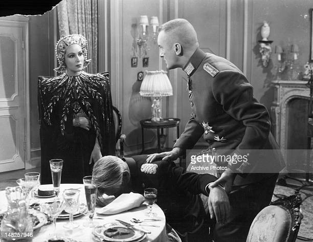 Dolores del Rio wearing head wear with jewel looking at George Sanders as he holds a passed out man's hand in a scene from the film 'Lancer Spy' 1937