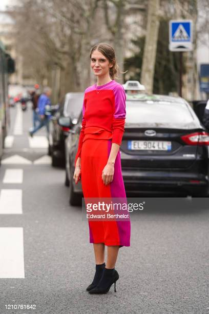 Dolores Doll wears a pink and red pullover, a colored skirt, black pointy shoes, outside Gauchere, during Paris Fashion Week - Womenswear Fall/Winter...